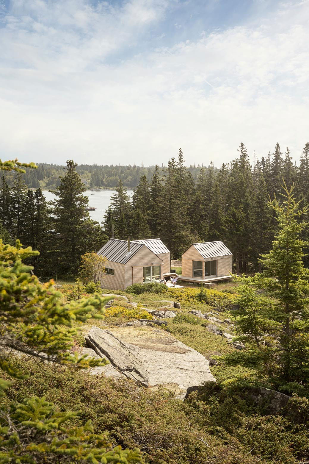 A Little House By A Lake Surrounded By Trees In Maine