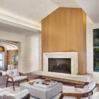Tall wooden fireplace wall becomes the focal point of this living room